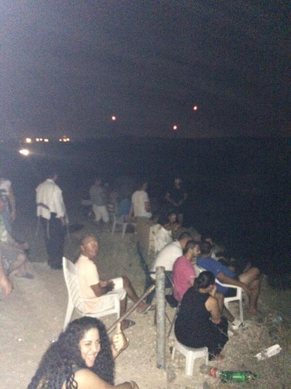 Israelis settling back in Sderot, enjoying watching the bombings of Gaza. They passed around pop corn while watching.