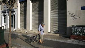 A Greek pensioner contemplating the future international finance capital poses for her.