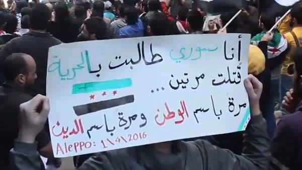 "A protester holds a sign up in a protest in Syria on April 1, 2016. The sign reads: ""I'm Syrian. I called for freedom. I was killed twice. Once in the name of the nation, once in the name of religion."""