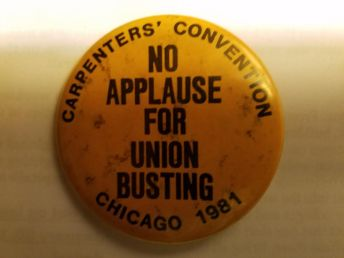 """No Applause for Union Busting"" Notice there is no union label - the union ""bug"" - on the button. The story behind this: Some delegates to the 1981 Carpenters Union convention got this button printed up in Chicago for when Reagan was set to appear. The union leadership got wind of it and called around to every union shop that made buttons and told them that if they printed up this button they never would get any union business again, so all the union shops refused the job so they were made at a non-union shop. Then, the Carpenters leadership refused to allow any delegates into the convention who were wearing a button without a union ""bug"".  Clearly, though, they have nothing against scabbing; it was just a ruse in order to be able to kiss up to the likes of Reagan (then) and Trump now."